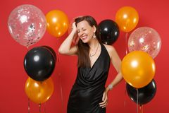 Smiling young girl with closed eyes in black dress celebrating, putting hand on head on bright red background air