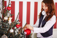 Smiling young girl decorating the Christmas tree Stock Images