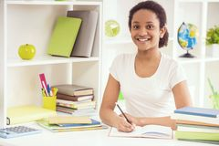 Smiling Young Girl Doing Homework on Table at Home stock photo