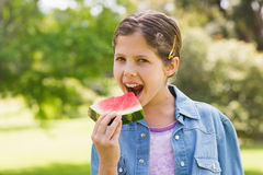 Smiling young girl eating water melon in park Stock Image