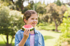 Smiling young girl eating water melon in park Stock Images