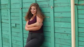 Portrait of a young girl overweight in the Park against the green wall. Girl XXL. Smiling young girl with excess weight poses in the park on the background of stock video