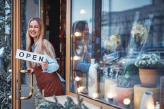 Smiling girl in the flower shop. Smiling young girl in the flower shop holding open sign Stock Photo