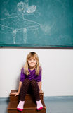 Smiling young girl in front of chalkboard Royalty Free Stock Photo