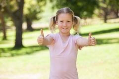Smiling young girl gesturing thumbs up at park. Portrait of a smiling young girl gesturing thumbs up at the park Stock Photography