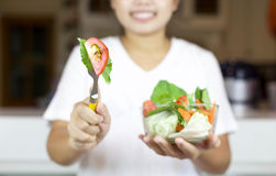 Smiling young girl hand holding fork with fresh salad Stock Photos