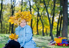 Smiling young girl with hat of autumn leaves Stock Photography