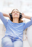 Smiling young girl in headphones at home Stock Images