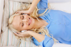 Smiling young girl in headphones at home Stock Photo