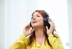 Smiling young girl in headphones at home Stock Photography
