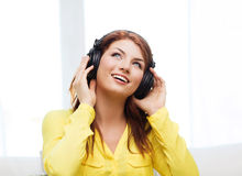 Smiling young girl in headphones at home Stock Photos
