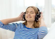 Smiling young girl in headphones at home Stock Image