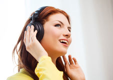 Smiling young girl in headphones at home royalty free stock images