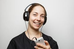 Smiling young girl with headphones listening to music from smartphone. And looking at camera Stock Photos