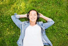 Smiling young girl in headphones lying on grass Stock Image