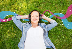 Smiling young girl in headphones lying on grass. Lifestyle, summer vacation, technology, music and people concept - smiling young girl in headphones lying with Stock Photography