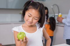 Smiling young girl holding apple with family in at kitchen. Smiling young girl holding apple with family in the background at kitchen in home Royalty Free Stock Image