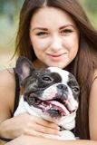Smiling young girl holding a bulldog Royalty Free Stock Photos