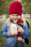 Smiling Young Girl Holding Cocoa Mug with Marsh Mallows Outside. Cute Smiling Young Girl Wearing Hat and Scarf Holding Cocoa Mug with Marsh Mallows Outside Royalty Free Stock Photos