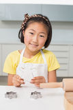 Smiling young girl holding cookie mold in kitchen Stock Image