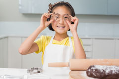 Smiling young girl holding cookie molds in kitchen Royalty Free Stock Photo