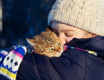 Smiling young girl holding her cat outdoors. Royalty Free Stock Photos