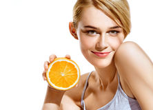Smiling young girl holding oranges halves on white background stock images