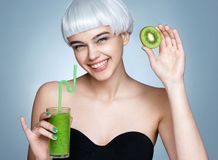 Smiling young girl holding smoothie detox cocktail of kiwi fruit. royalty free stock images