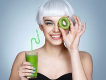 Smiling young girl holding smoothie detox cocktail of kiwi fruit Royalty Free Stock Image