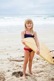 Smiling young girl holding surfboard on beach Royalty Free Stock Photos