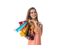 Smiling young girl keeps on his shoulder a lot of bright gift packages, isolated  white background Stock Photo