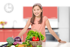 Smiling young girl in a kitchen, standing behind a pile vegetabl Stock Image