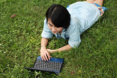 A smiling young girl with laptop outdoors Stock Image
