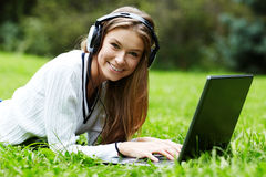 A smiling young girl with laptop outdoors listening music by hea Royalty Free Stock Images