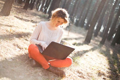Smiling young girl with laptop outdoors Stock Photos