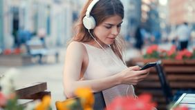 Young girl listen to music on the bench. Smiling young girl listen to music on headphones on the bench Stock Photos