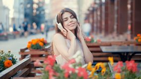 Smiling young girl listen to music on headphones. Outdoors Stock Image
