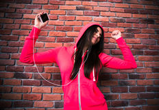 Smiling young girl listening music and dancing in headphones Stock Images