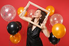 Smiling young girl in little black dress celebrating, looking up, holding picture frame on bright red background air royalty free stock photo
