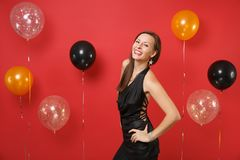 Smiling young girl in little black dress celebrating standing with arms akimbo on bright red background air balloons. St