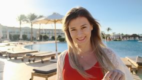 Smiling young girl, looking at camera. Beautiful woman in red swimsuit near the blue swimming pool on hot sunny day. Girl having good time, summer holiday at stock video