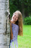 Smiling young girl looks out from the tree Stock Photos