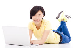 Smiling young girl lying on the floor with a laptop Stock Image