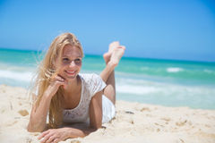 Smiling young girl lying on the sunny beach Stock Image