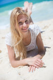 Smiling young girl lying on the sunny beach Stock Photo