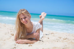 Smiling young girl lying on the sunny beach Royalty Free Stock Image