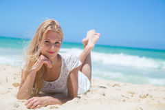 Smiling young girl lying on the sunny beach Royalty Free Stock Images