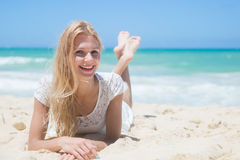 Smiling young girl lying on the sunny beach Stock Images