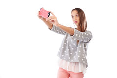 Smiling young girl making selfie photo and puckering lips at the Royalty Free Stock Image