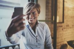 Smiling young girl making selfie on smartphone device while spending time in living room.Attractive woman owner. Communicating on cellular phone.Blurred Royalty Free Stock Photos